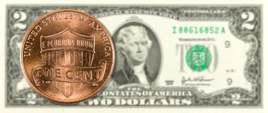 1 cent coins against 2 us-dollar bank note obverse royalty free stock photo