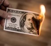 Cent dollars de brûlure en flammes à disposition Photographie stock libre de droits