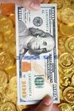 Cent dollars en main et pièces de monnaie Photo stock