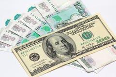 Cent dollars et cinq mille billets de banque de rouble Photos stock