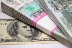 Cent dollars et deux paquets à mille billets de banque de rouble Images stock