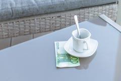Cent euro et vides tasses de café sur une table en verre de café extérieur Paiement, astuce photographie stock libre de droits