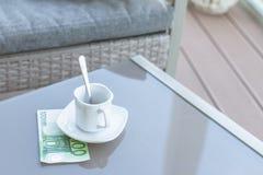 Cent euro et vides tasses de café sur une table en verre de café extérieur Paiement, astuce photo stock