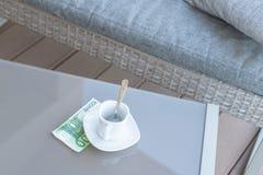 Cent euro et vides tasses de café sur une table en verre de café extérieur Paiement, astuce image stock
