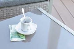 Cent euro et vides tasses de café sur une table en verre de café extérieur Paiement, astuce photographie stock
