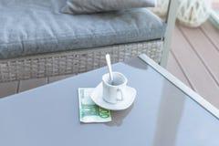 Cent euro et vides tasses de café sur une table en verre de café extérieur Paiement, astuce image libre de droits