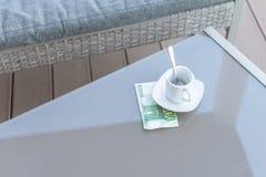Cent euro et vides tasses de café sur une table en verre de café extérieur Paiement, astuce photo libre de droits