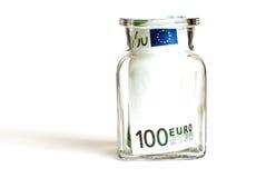 Cent euros dans un pot en verre, sur un fond blanc Images stock