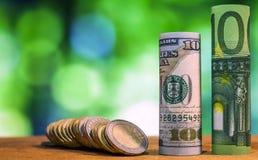 Cent euros et cent dollars US ont roulé le billet de banque de factures Image libre de droits
