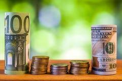 Cent euros et cent dollars US ont roulé le billet de banque de factures Images libres de droits