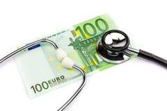 Cent notes d'euro avec le stéthoscope professionnel sur le backgro blanc Photo stock