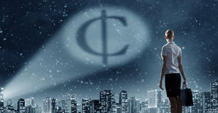 Cent symbol in dark sky. Businesswoman standing with back and cent sign in spotlight stock photos