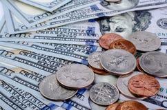Centavos de diversas denominaciones encima de cientos billetes de dólar Fotografía de archivo libre de regalías