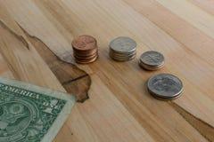 Centavos de la moneda de los E.E.U.U. en pilas y billete de dólar en la tabla de madera