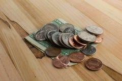 Centavos de la moneda de los E.E.U.U. encima del billete de dólar en la tabla de madera
