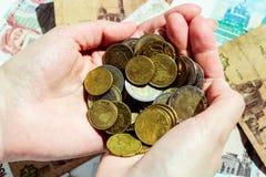 Centavos do Euro e de Euro nas mãos fêmeas com fundo da cédula foto de stock