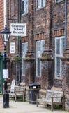 CENTEIO, Reino Unido/ø de junho de 2014 - os bancos de madeira na rua pelos registros da escola secundária compram Fotografia de Stock