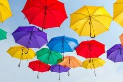 Centenares coloridos brillantes de paraguas que flotan sobre la calle Foto de archivo