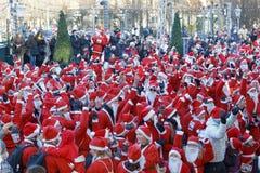 Centenares de bailar Santas en vestidos y barba rojos tradicionales foto de archivo