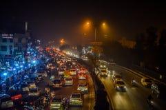 Centenares de coches en un tráfico durante noche con niebla con humo arriba en el Ne fotos de archivo