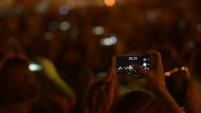 Centenares de gente que hace los vídeos de fuegos artificiales en sus smartphones en festival de música almacen de video