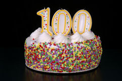 Centenarian Celebration 2. A colorful birthday cake with candles shaped like the number 100. Black background royalty free stock images