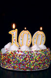 Centenarian Celebration 3. A colorful birthday cake with candles shaped like the number 100. Black background Stock Photos