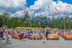 Centenas de balões coloridos em um céu azul contra um fundo das nuvens fotografia de stock