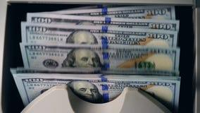 Centenas de dólares contados em um verificador de trabalho da moeda filme
