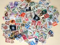 Centenas de selos de porte postal internacionais Foto de Stock