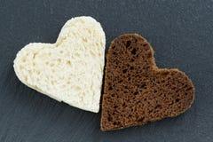 Centeno y pan blanco tostados bajo la forma de corazón en oscuridad Fotos de archivo libres de regalías
