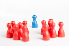Center of attention blue pawn surrounded  by red pawns Royalty Free Stock Images