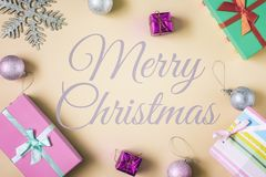 In the center of a beige background, the inscription is Merry Christmas. Spread around the boxes with gifts and royalty free stock photography
