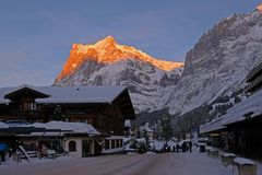Center of the Grindelwald village with the mountain Wetterhorn at dusk, the street is snow covered, Bern, Switzerland royalty free stock photography