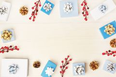 In the center of the light background, Copy Space. Christmas composition, frame. White and blue gift boxes with bows. Red decorative berries and cones. Festive royalty free stock photos