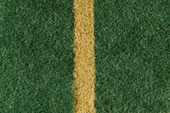 Center line on football field, yellow marking on artificial gras Royalty Free Stock Photos