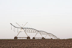 A center modern pivot irrigation system. In a cultivated land farm field Royalty Free Stock Photography