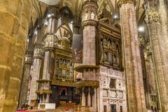 The huge pipe organ of the Duomo di Milano. The center nave of the Gothic cathedral in Milan with it`s majestic columns, arches and stained glass windows, and stock images