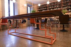 In center of photo unusual table in middle of modern restaurant. In middle of establishment, cafe or restaurant table with wooden lacquered top on unusual metal Royalty Free Stock Photo
