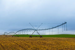 Center pivot irrigation system in brown field Stock Images