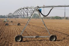 Center pivot irrigation system in a plowed field on a sunny day Stock Images