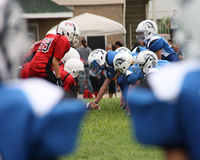 Center preparing to snap the ball. Royalty Free Stock Images