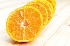 Center (Selected focus) of orange half which is the first of lin. E and other oranges on wood ground Stock Photos
