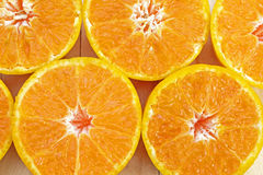 Center (Selected focus) of orange half which is at left below si. De of frame and other oranges on wood ground Stock Photo