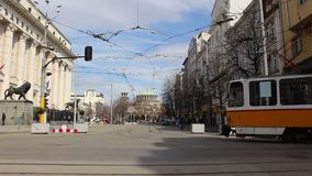 The center of Sofia - passing trams in the back of the church St. Nedelya spring March 2019 Bulgaria. This video was taken in Sofia, in Bulgaria winter-spring stock video footage