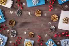 In the center of the wooden background Copy space. Around neatly laid out the twigs of red berries, small gift boxes royalty free stock image