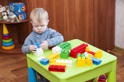 Centered child plays with a toy constructor constructor Stock Photos