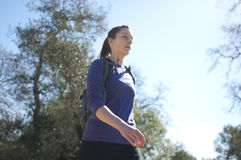 Centered close up of woman hiking in blue shirt facing right. On a sunny day Stock Image