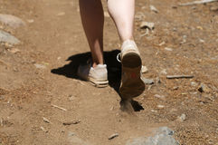 Centered close up of woman's feet hiking in dirt. On a sunny day Royalty Free Stock Photos