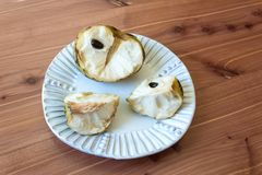 Centered white plate with one half and two quarters of a ripe cherimoya fruit Annona cherimola. Central stem and seeds, horizontal aspect Royalty Free Stock Image